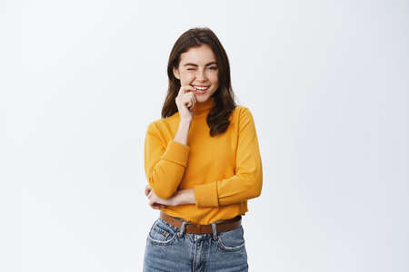 Successful smiling woman biting finger and winking at you with coquettish and flirty face, standing in yellow sweater with self-assured face, white background
