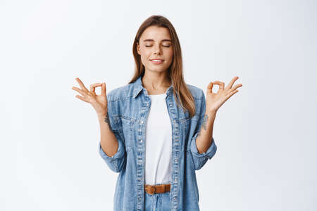 Feeling zen in body. Relaxed young woman standing calm and peaceful in meditating pose, close eyes and breathing, standing against white background