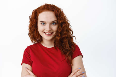 Close-up portrait of confident woman with ginger curly hair, cross arms on chest and smiling, have pale skin without blemishes and blue eyes, white background