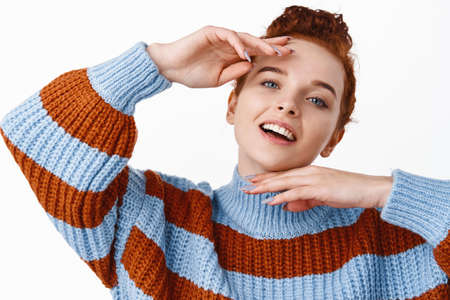 Portrait of redhead woman beautiful pale face, touching clean fresh and smooth skin after cosmetic products against blemishes and acne, standing over white background
