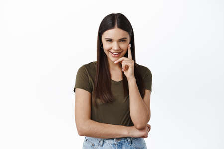 Image of cunning thoughtful woman giggle and squint at camera while looking mysteriously, have idea, make-up a plan, standing devious against white background