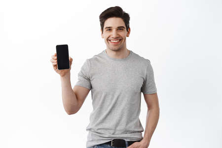 Caucasian handsome man show mobile phone screen, smiling and giving app recommendation, standing in t-shirt against white background