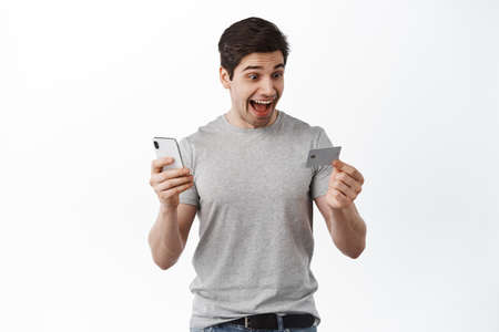Guy screams and looks at credit card, order online, paying with smartphone, purchase in internet, standing over white background
