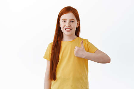 Portrait of ginger girl with cute toothy smile, shows thumb up in approval, like and agree, say yes, give positive reply, recommend something good, praise excellent job, white background