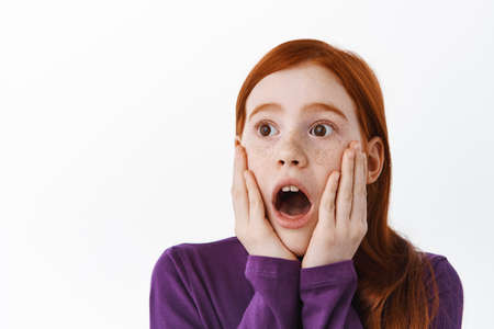 Surprised redhead little kid, girl with ginger hair and freckles gasping, staring aside with shocked face, standing over white background