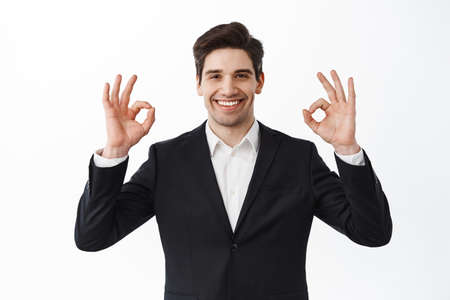 Very good. Smiling satisfied businessman, male entrepreneur in business suit, show okay signs and nod in approval, say yes, agree and praise work, white background Stockfoto