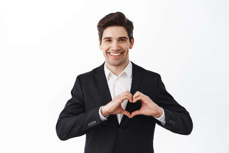 Handsome groom, boyfriend in black suit, show heart sign and smiling, say I love you, express admiration and heartfelt feeling, standing over white background