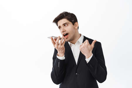 Corporate man talking speakerphone and counting on fingers, give instructions during phone call, standing with smartphone against white background