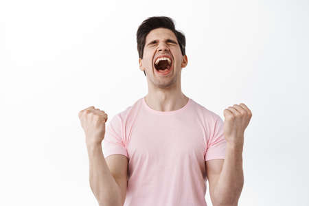 Happy man screams in celebration, winning prize, shouting with joy, clench fists like champion, celebrating victory and triumph, achieve goal success, standing over white background