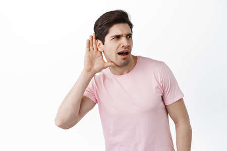 Gossip man trying to overhear someone, hold hand near ear and lean closer to copy space, trying to understand words, eavesdropping, standing over white background