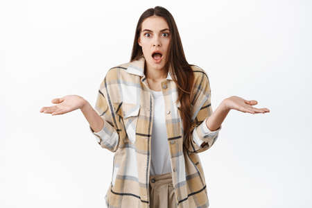 Surprised and confused woman gasp wondered, shrugging and stretch hands sideways clueless, dont know nothing, have no idea, cant understand what happened, white background