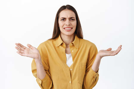 Thats nonsense ridiculous. Confused and annoyed woman spread hands sideways, shrugging and grimacing bothered, cant understand whats matter, why though, standing over white background