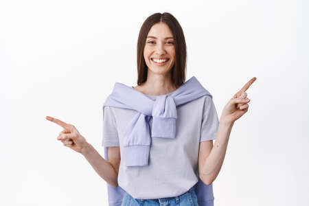 Smiling brunette lady in spring casual outfit, pointing sideways, showing copy space  banner, two variants, choices of products, standing against white background 版權商用圖片