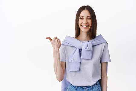 Take look there. Smiling friendly girl pointing thumb aside, showing left promo deal, copy space, wearing spring purple outfit, standing against white background 版權商用圖片