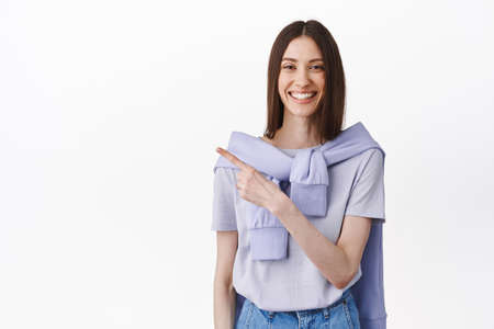 This way, look. Smiling friendly pretty girl pointing finger aside, showing advertisement on left copy space, introduce product, demonstrate promotional text, standing over white background 版權商用圖片