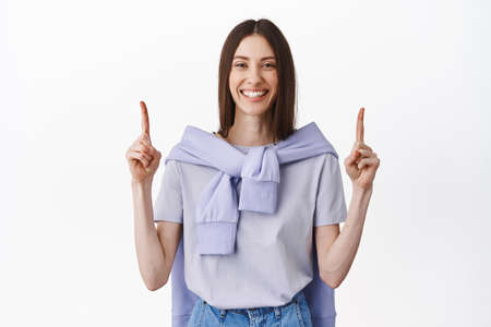 Read this sign above. Smiling friendly girl pointing fingers up, showing best promotional deal, shopping link or website, standing over white background