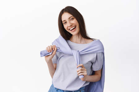 Joyful smiling girl put sweatshirt around neck, going on evening walk in spring, looking happy and carefree, standing over white background 版權商用圖片