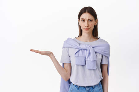 Skeptical and doubtful girl holding empty space product on open hand, look with doubt and dislike, frowning displeased, display bad item to purchase, stands against white background