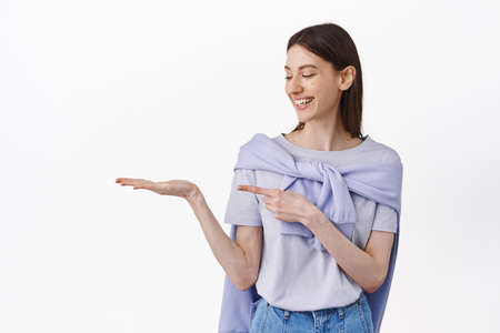 Let me introduce you this. Pretty young woman looking at her open hand holding logo product, pointing at empty space on her palm, showing something, white background