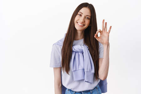 Everything okay. Smiling brunette woman showing ok sign, approve and agree, praise excellent job, good, work, approve something, standing over white background 版權商用圖片