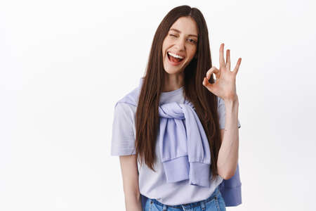 Yes Okay. Cheerful brunette woman winking, smiling and showing ok gesture, approve and agree, like something, praise nice work, perfect choice, standing over white background