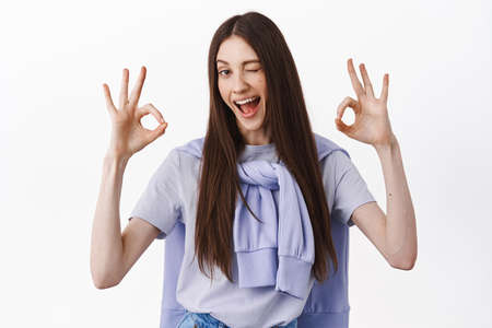No problem, excellent. Brunette girl winking and showing okay gesture, OK sign, like and approve, assure everything good, under control, standing over white background 版權商用圖片