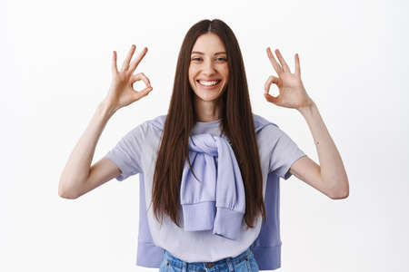 Totally agree. Attractive caucasian woman showing OK okay gesture, nod and agree, give positive answer, praise perfect choice, make compliment, standing over white background