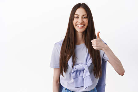 Positive feedback. Smiling brunette woman showing thumb up, nod in approval, support good choice, praise great work, excellent thing, standing over white background