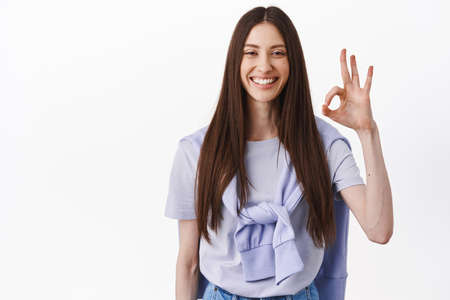 Very well, good work. Smiling brunette girl show OK okay sign in approval, nod and agree, give positive answer, praise excellent choice, standing in t-shirt against white background 版權商用圖片