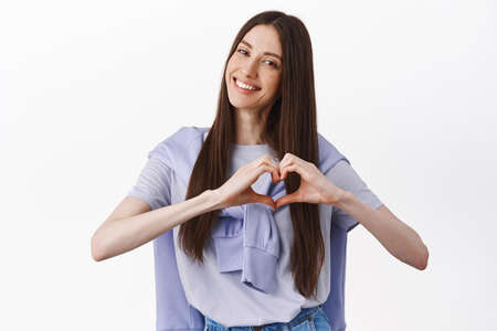 Like it. Smiling cute young woman showing heart gesture, tilt head and look adorable, I love you sign, standing against white background
