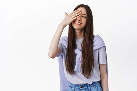 Beautiful young brunette woman smiling, covering one eye and look adorable at camera, standing in t-shirt against white background 版權商用圖片