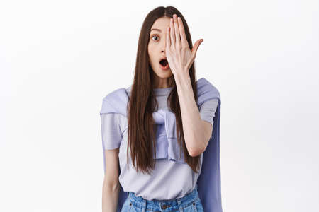 Girl looks surprised with half side of face closed palm, staring amazed at camera, checking out something cool, standing over white background