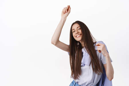 Positive teenage girl having fun, dancing and enjoying party, celebrating, standing over white background