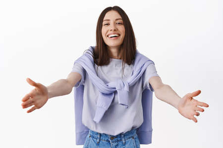 Come here. Smiling friendly woman stretching hands out for hug, reaching to hold something, standing over white background