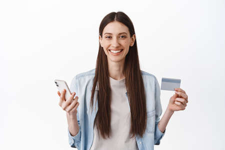 Image of young female model holding credit card and smartphone, concept of online shopping, contactless payment and internet delivery, standing over white background