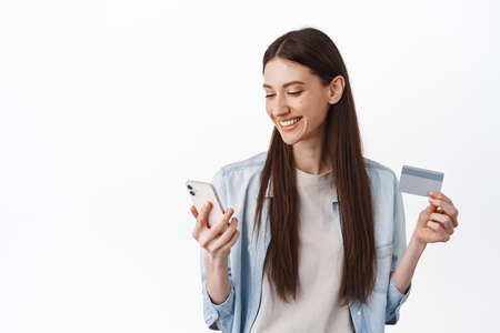 Young woman paying with credit card and smartphone. Girl looks at her phone and smiles, shops online, checking bank account, standing over white background 版權商用圖片