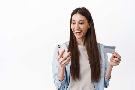 Portrait of brunette girl looks excited at smatphone screen, reading proo offer online, paying contactless and making order in phone with credit card 版權商用圖片