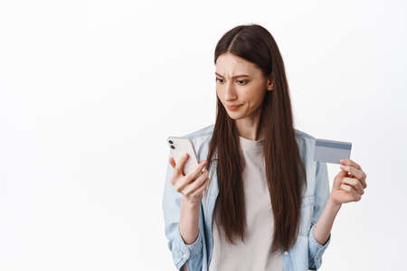 Online shopping. Woman looks confused at smartphone while checking bank account, holding credit card, order in internet, standing over white background
