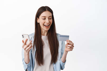 Online shopping. Smiling brunette girl paying with credit card and smartphone, laughing and looking pleased, placing an order in app, standing over white background