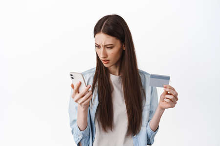Online shopping. Brunette girl looks confused at smartphone screen, holding credit card, cant understand how register card to place an order, standing over white background