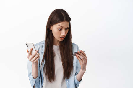 Online shopping. Woman holds smartphone and looks confused at credit card, have no money, checking her bank account in app, standing over white background