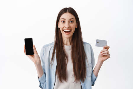 Super happy woman showing her empty smartphone screen and credit card, paying online, shopping in application, standing over white background
