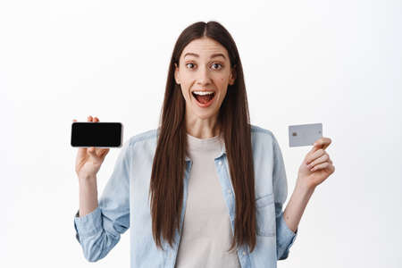 Happy brunette girl student shows her smartphone horizontal screen, credit card, smiling amazed, shopping online, paying in internet, standing over white background