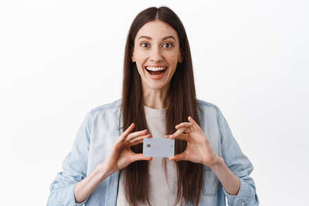 Image of happy brunette woman looking amazed, showing credit card, bank or shopping advertisement, standing over white background