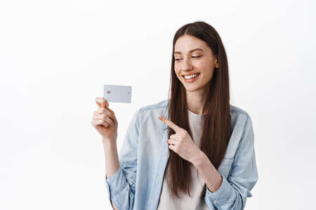 Modern girl smiling, pointing and looking at credit card, recommending bank, contactless payment during pandemic, standing over white background