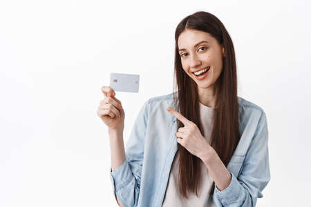 Check this card. Sassy cool girl, pointing at credit card and smiling, recommending bank, standing in casual clothes against white background 版權商用圖片
