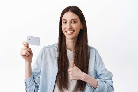 Cheerful brunette girl show credit card and thumbs up, recommending bank, praise contactless easy payment, good discounts, standing over white background