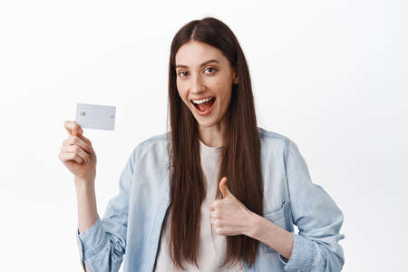 Image of female student say yes, showing credit card and thumb up, approve and recommend bank, easy contactless payment, standing over white background 版權商用圖片