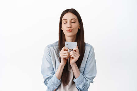 Silly romantic girl, waiting for shopping, kissing her credit card with closed eyes, standing against white background