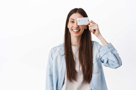Image of smiling brunette girl, showing credit card near face and looking positive, standing against white background